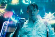 Man wearing white polo holding a futuristic item in a sci-fi movie