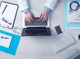 man typing on his laptop