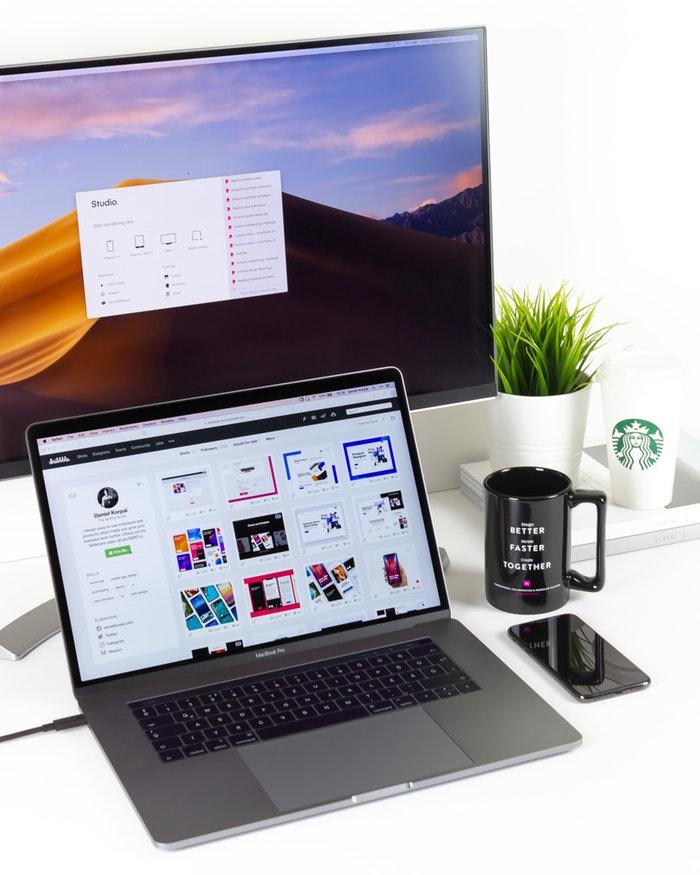 aptop near mug and computer monitor