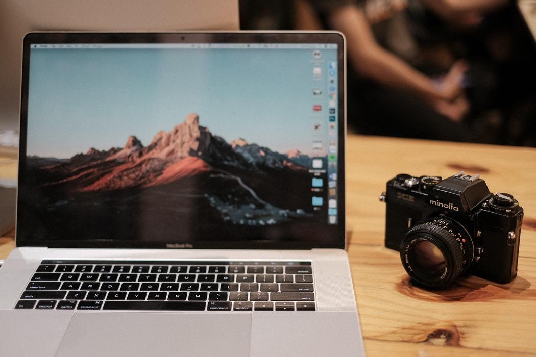 MacBook Pro with touchbar beside black Minolta DSLR camera