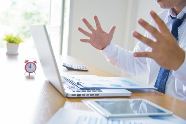 Young stressed handsome businessman working at desk in modern of