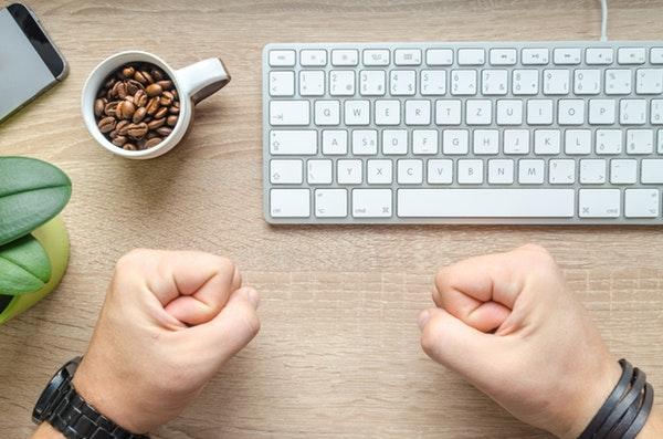 Closed fist near a white keyboard
