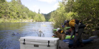 A Yeti cooler on the bank of a river, which is one of the best can coolers you can buy.