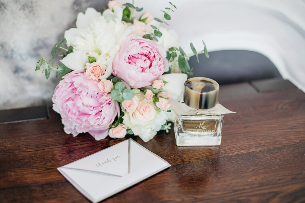 A stack of gifts for women, including a card, flowers, and a present.