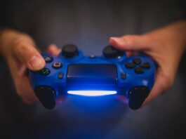 A man holding a light up controller, whis is one of the best PS4 accessories