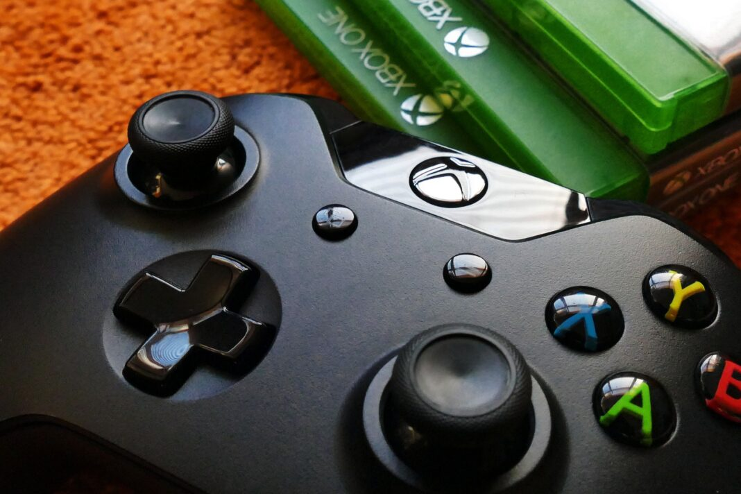 A controller, which is one best xbox one accessories, and a stack of game boxes.
